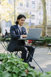 USA, New York City, Manhattan, smiling businessman working with a laptop in Bryant Park - GIOF000247