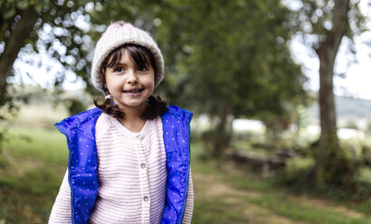 Portrait of smiling little girl wearing woolly hat and waistcoat - MGOF000807