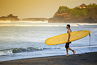 Indonesia, Bali, surfer walking on the beach - KNTF000103
