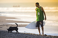 Indonesia, Bali, surfer and dog on the beach - KNTF000106
