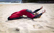 Spain, Asturias, Colunga, surfer stretching on the beach - MGOF000834