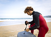 Spain, Asturias, Colunga, surfer preparing bodyboard on the beach - MGOF000837