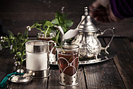 Pouring sugar into traditional North African tea with fresh mint leaves - SBDF002289