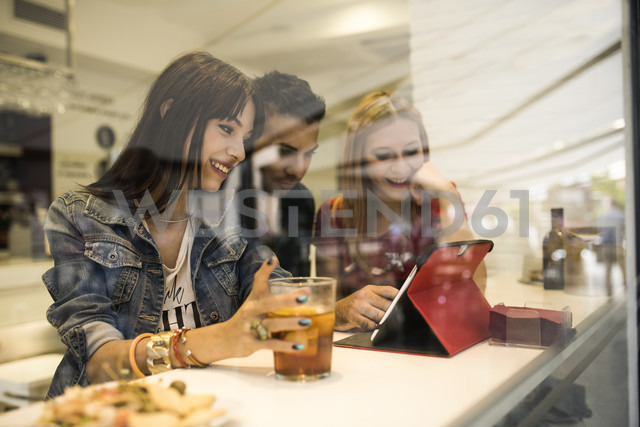 Three friends in a bar with drinks using digital tablet - JASF000136 - Jaen Stock/Westend61