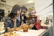 Three friends in a bar with drinks using digital tablet - JASF000136