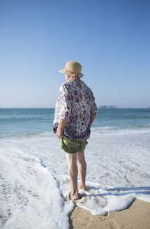 Spain, Ferrol, back view of senior woman standing on the beach - RAEF000528