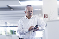 Businessman in open space office using smartphone - SGF001896