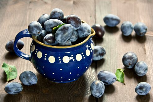 Plums on wood and in blue jar - YFF000461