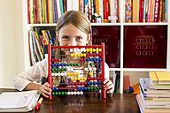 Smiling little girl sitting behind abacus - SARF002177