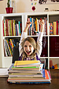 Portrait of cheering girl sitting behind stack of school books - SARF002180