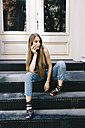 Pensive young woman sitting on stairs in front of an entry door - GIOF000255