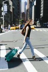 USA, New York City, young woman with rolling suitcase crossing a street - GIOF000261