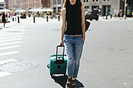 USA, New York City, young woman with rolling suitcase standing on  street - GIOF000264