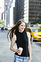 USA, New York City, portrait of laughing young woman with coffee to go - GIOF000267