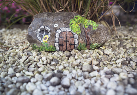 Stone painted as little house in garden - OPF000081