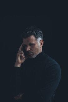 Portrait of pensive man wearing black turtlenack in front of black background - CHAF001479
