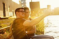Germany, Muenster, couple taking a selfie with smartphone at backlight - TAM000274