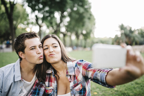 Portrait of young couple in love taking a selfie with smartphone in a park - JRFF000126