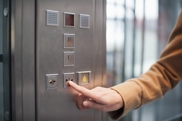 Woman pressing button of a lift - NNF000297