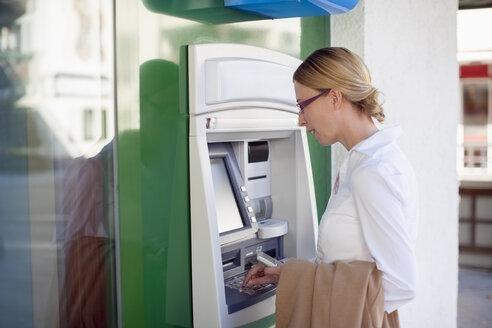 Woman using cash machine - NNF000300