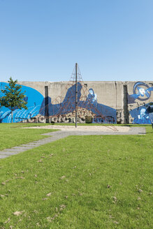 Germany, Duisburg RheinPark, Jungle gym on playground in front of wall with graffiti - VI000428