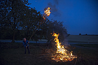 Germany, boy at camp fire on a meadow in the evening - SARF002200