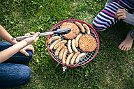 Boy and girl barbecuing sausages and meat n garden - SARF002203