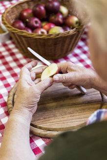 Senior woman cutting apples, close-up - MIDF000687