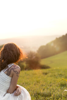Germany, Baden-Wuerttemberg, Black Forest, back view of woman on Alpine meadow watching sunrise - MIDF000699