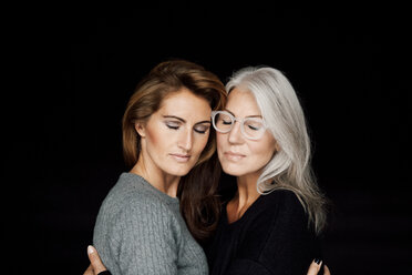 Two women with closed eyes head to head in front of black background - CHAF001521
