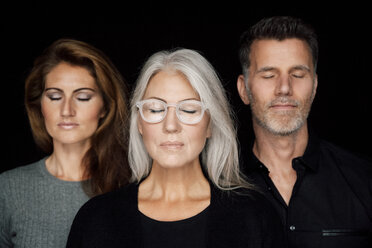 Portrait of three people with closed eyes in front of black background - CHAF001524