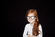 Portrait of redheaded smiling little girl wearing oversized glasses in front of black background - CHAF001530