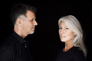 Portrait of mature man and mature woman wearing black clothes in front of black background - CHAF001533