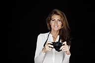 Portrait of smiling woman with camera in front of black background - CHAF001542