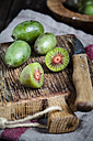 Sliced and whole mini kiwis and a kitchen knife on wooden chopping board - SBDF002300