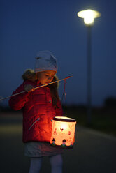 Portrait of little girl with lighted paper lantern on St. Martin's Day at twilight - LBF001248