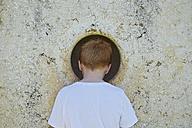 Boy peeking through hole in wall - JEDF000254