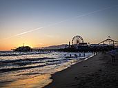 USA, Los Angeles, view to Santa Monica pier and Pacific Park at sunset - SBDF002307