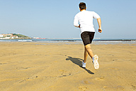 Spain, Asturias, Gijon, young man running on the beach - MGOF000840