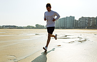 Spain, Asturias, Gijon, young man running on the beach - MGOF000843