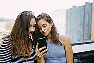 USA, New York City, two friends looking at cell phone - GIOF000281