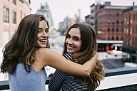 USA, New York City, two friends embracing in the city - GIOF000284