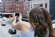 USA, New York City, friends taking a selfie with cell phone - GIOF000287