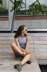 Brunette young woman wearing sunglasses relaxing on bench - GIOF000296