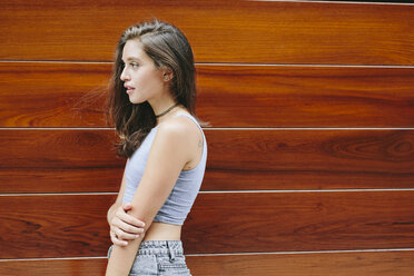 Brunette young woman at wooden wall - GIOF000308