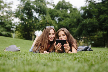 Two friends in a park looking at cell phone - GIOF000317