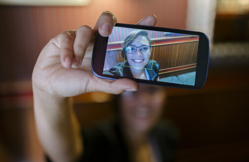 Photo on display of a smartphone of young woman taking a selfie - MGOF000849