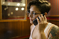 Tattooed young woman sitting in a coffee shop talking on phone - MGOF000852
