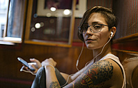 Portrait of tattooed young woman listening music with earphones - MGOF000861