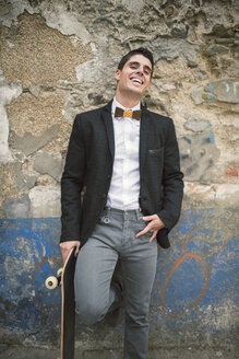 Portrait of young man with skateboard wearing jacket and a wooden bow tie - RAEF000546
